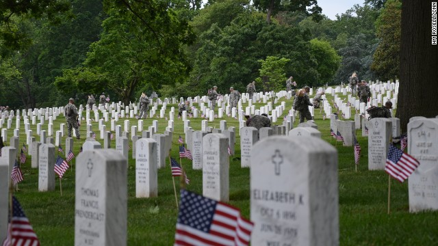 """Members of the Army's 3rd Infantry Regiment -- also known as the """"Old Guard"""" -- plant flags at tombstones in Arlington National Cemetery in Washington on Thursday, May 23, ahead of Memorial Day."""