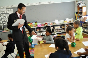 Providence Mayor Angel Taveras hands out books to young students during a school visit.