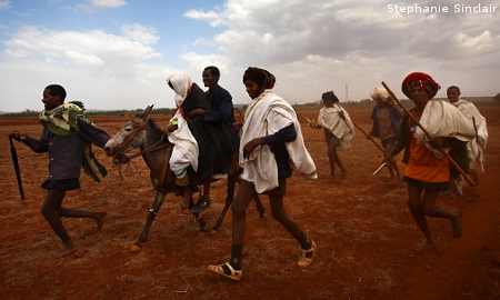 Leyualem, 14, is wisked away on a mule by her new groom and groomsmen in Ethiopia.