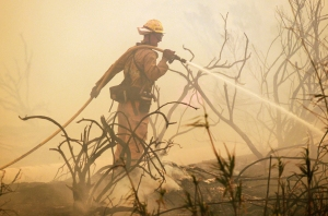 A firefighter sprays water on a flare up as a wildfire burns along the Pacific Coast Highwayon  May 3, 2013.  Photo credit: ROBYN BECK/AFP/Getty Images)