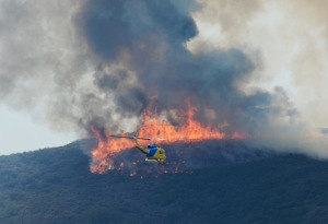 A Ventura County Fire Department helicopter heads to make a water drop on the wildfire in Pt. Mugu State Park on May 3, 2013. Photo credit: Kevork Djansezian/Getty Images