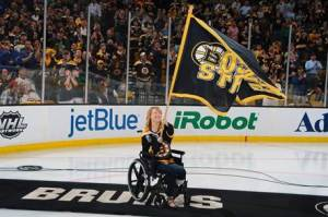 "Adrianne Haslet-Davis waves a ""Boston Strong"" flag at a Bruins playoff game. Source: Getty"